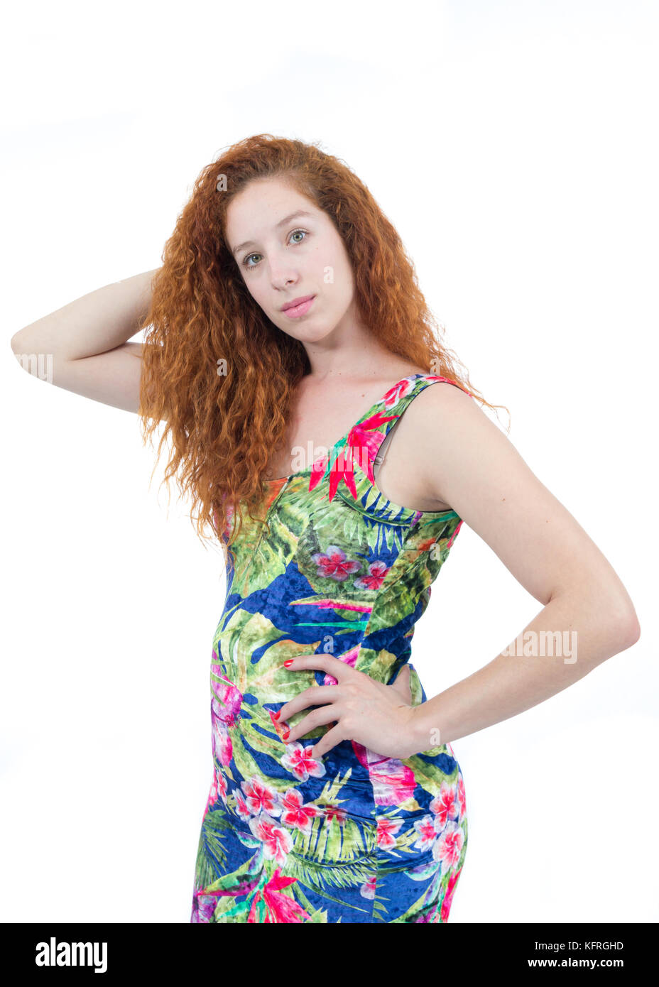 Young woman stands with hand on waist and looks at camera. Redhead teenager with wavy hair. Tropical print dress. - Stock Image