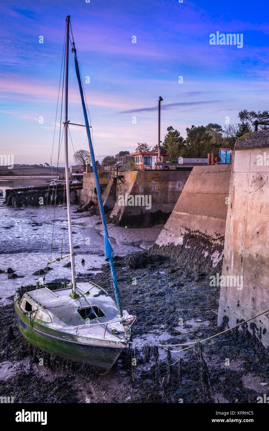 A long forgotten sailing boat is left to rot next to the entrance of the old shipyard in Appledore, North Devon. - Stock Image