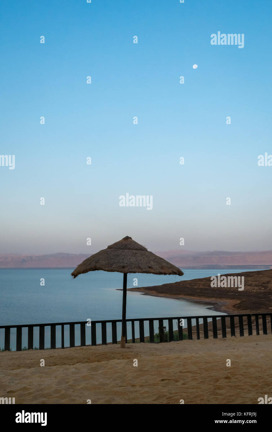 Early morning with moon in the sky at Holiday Inn Dead Sea resort, no people on the beach and straw umbrella, Jordan, - Stock Image