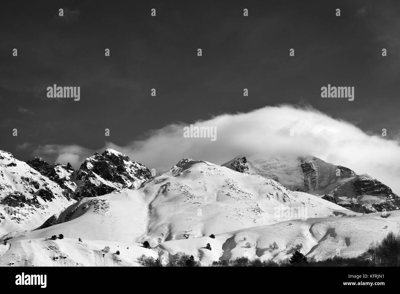 Black and white mountains in clouds and off-piste slope in winter. Caucasus Mountains, Mount Tetnuldi, Svaneti region - Stock Image