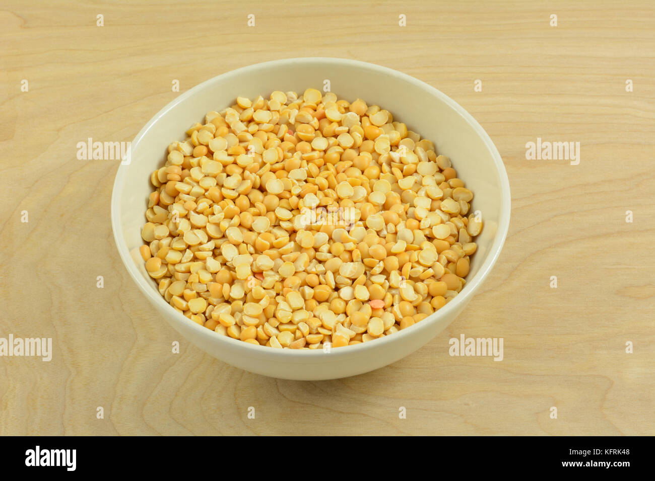 Dry raw yellow split peas in white bowl on wooden table - Stock Image