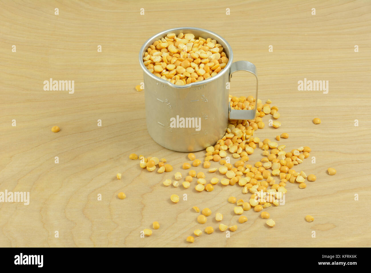 Antique retro measuring cup full of dry raw yellow spit peas - Stock Image