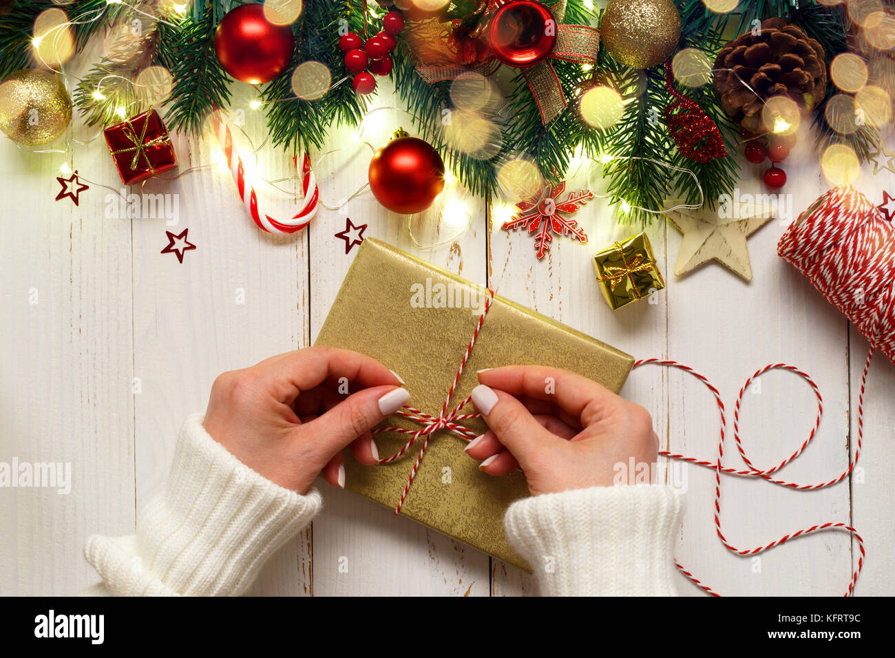 woman's hands tying up christmas gift box on white wooden table with festive ornaments and lights Stock Photo