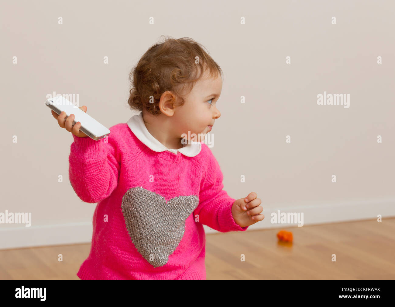 Toddler baby girl plays with smart phone. Concept of social problem. - Stock Image