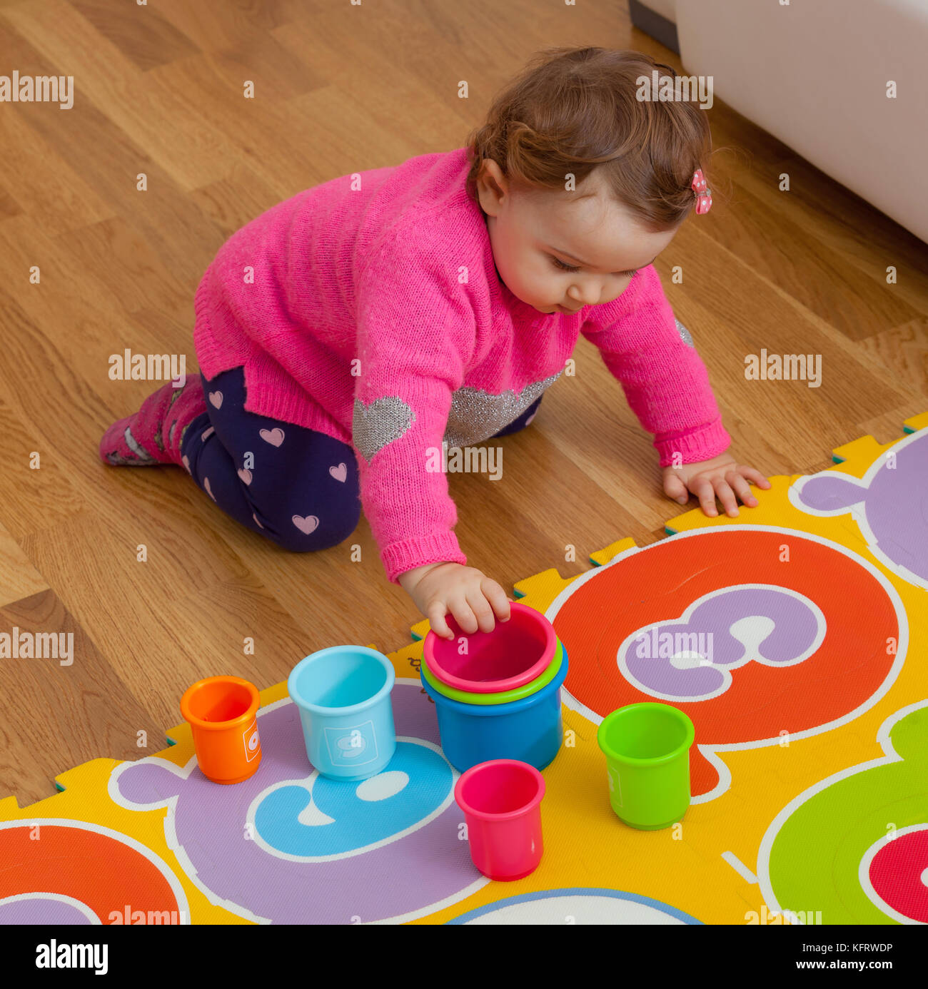 Toddler Baby Girl Plays With Colored Cups Toy For