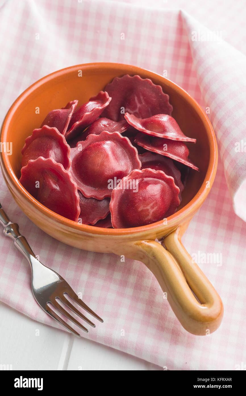 Tasty beetroot ravioli in bowl. - Stock Image