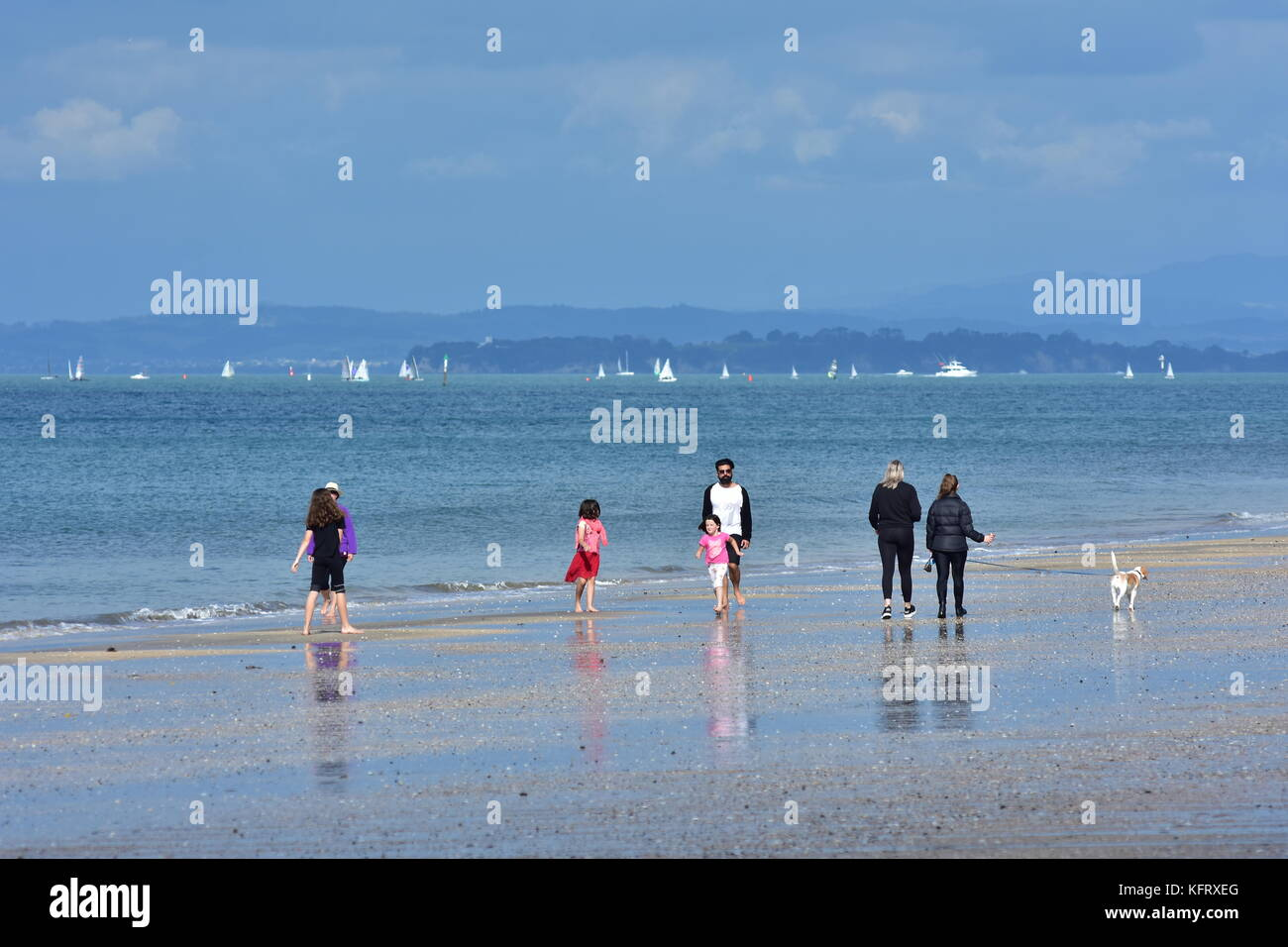 People walking on flat sandy ocean beach of Takapuna in Auckland on cloudy day. - Stock Image
