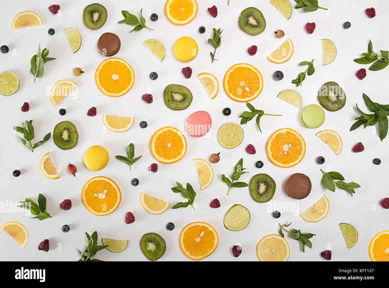 Flat lay still life with macarons, berries, mint and citrus and other fruits: orange fruit; lime; lemon, kiwi on - Stock Image