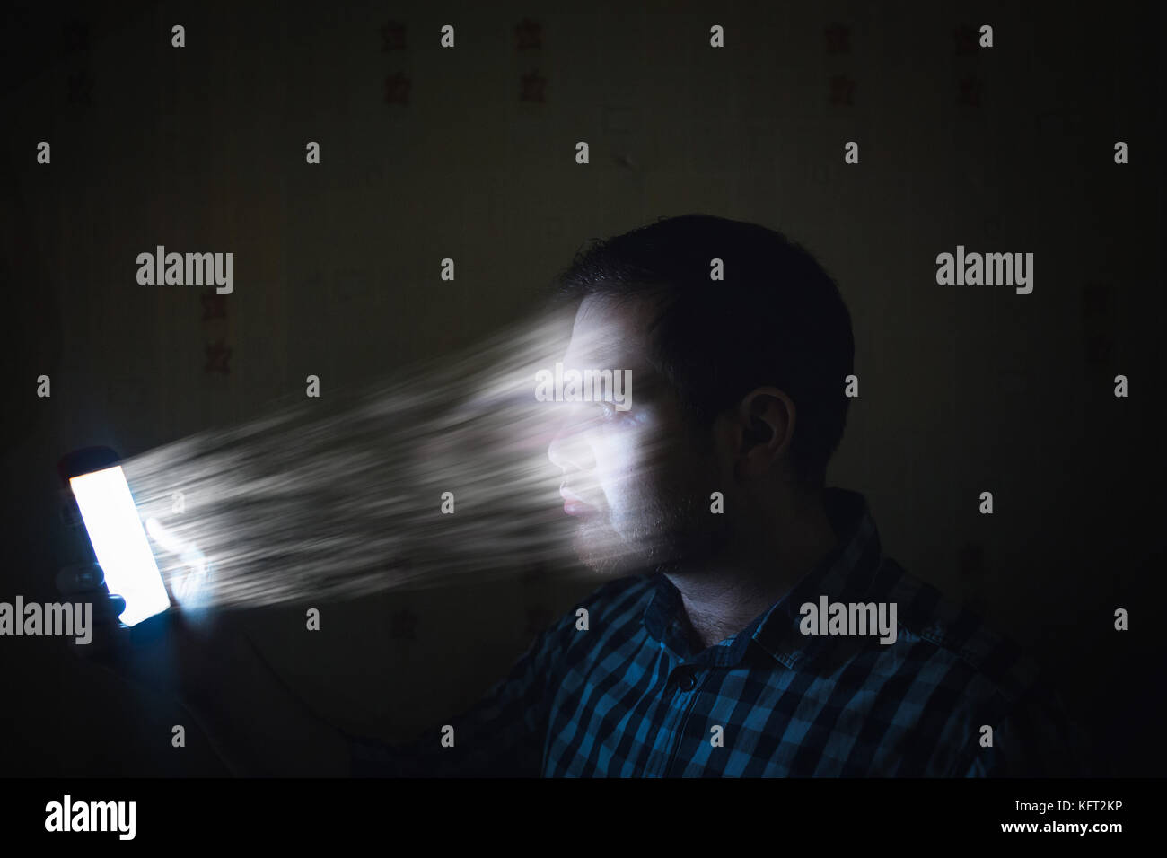 Concept Internet of dependence, submission. Man sucked into a phone. The man's face is transferred to the smartphone - Stock Image