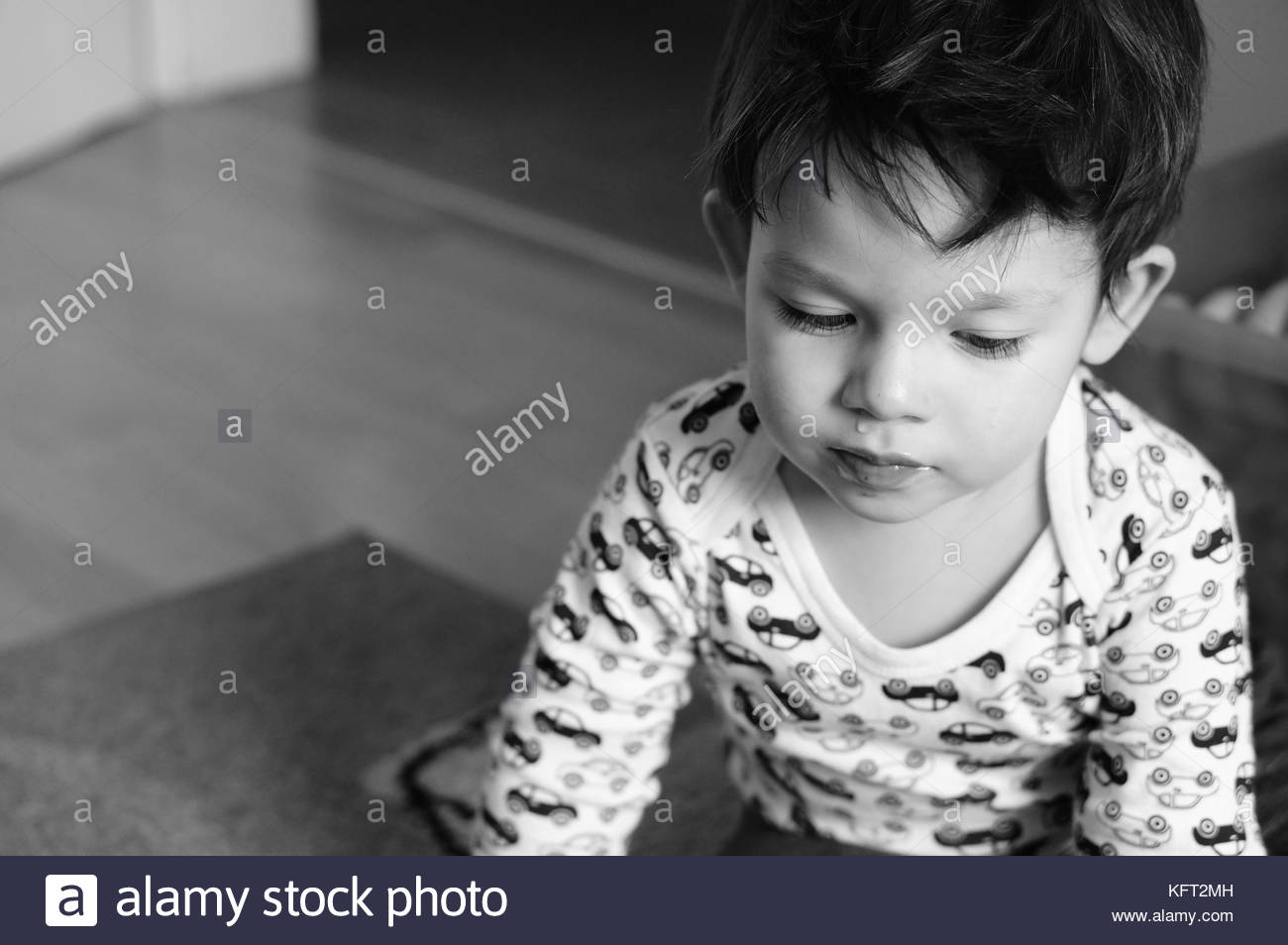 Sick baby with cold sitting on the floor - Stock Image