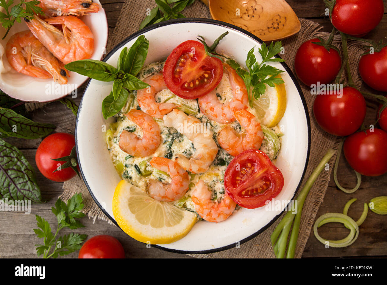 Overhead of dinner table. Seefood casserole with leek, cheese, grilled shrimps, serving with tomato cherry, parsley - Stock Image
