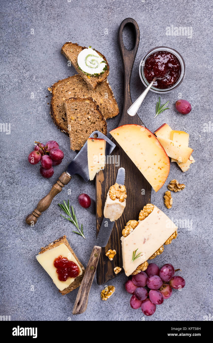 Assorted cheeses on wooden board - Stock Image