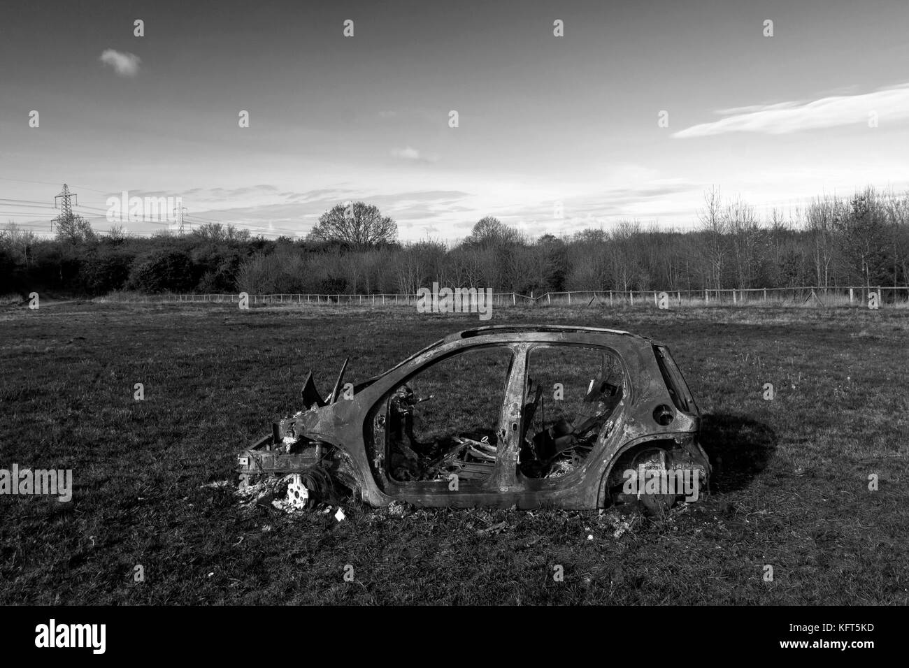 car crime - a stolen & burned out car left in a field. - Stock Image