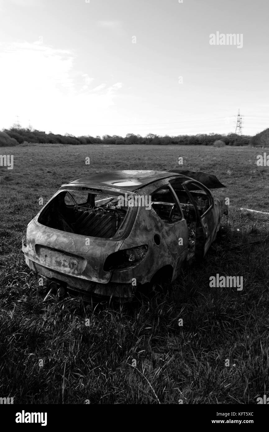 car crime - a stolen & burned out car left in a field. Stock Photo