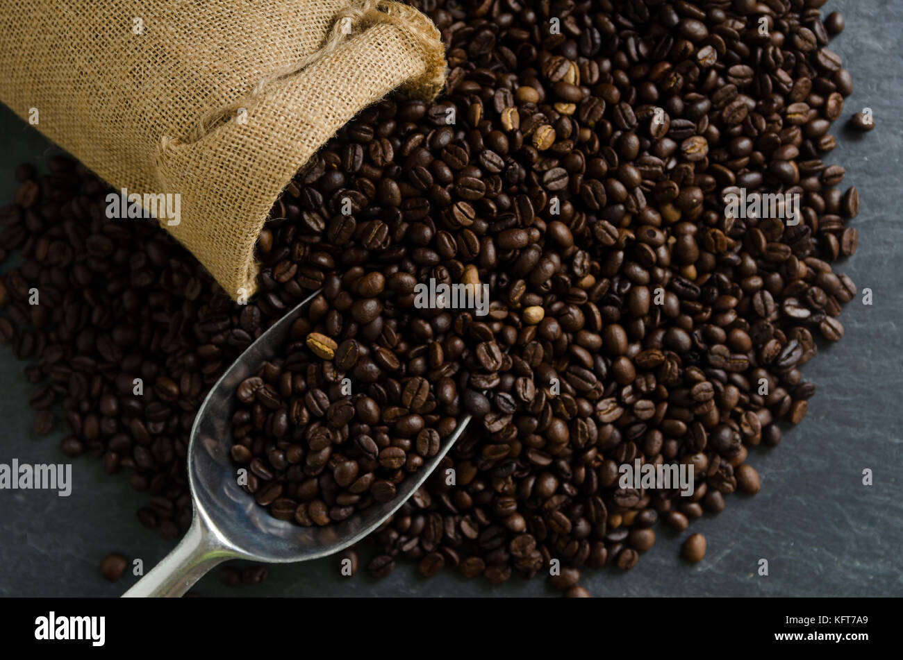 Coffee cup and roasted coffee beans in burlap sack bag with leaves on black granite background - Stock Image
