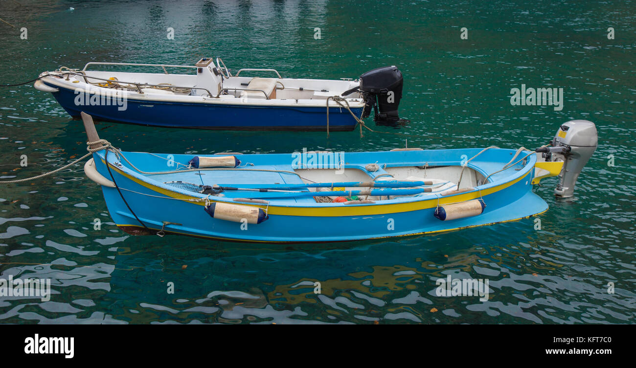 Two small fishing boats anchored at the pier. - Stock Image