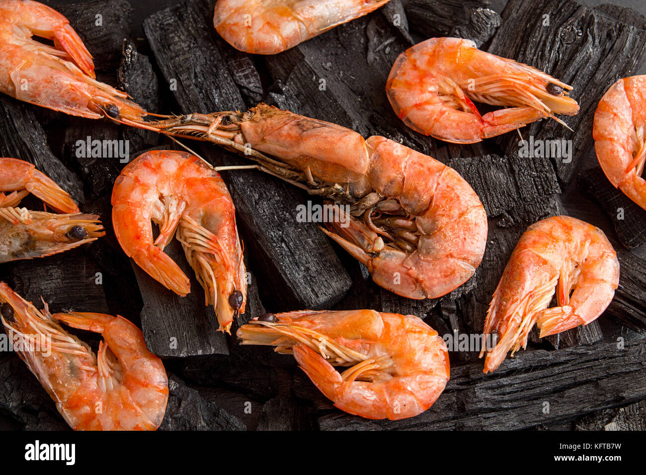 Overhead shrimps on charcoal. Seefood barbecue concept. Healthy diet food. Top view - Stock Image