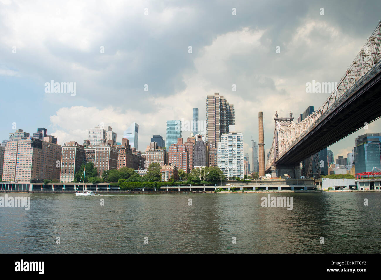 New York City and Queensboro Bridge skyline viewed across the East River from Roosevelt Island waterfront. - Stock Image