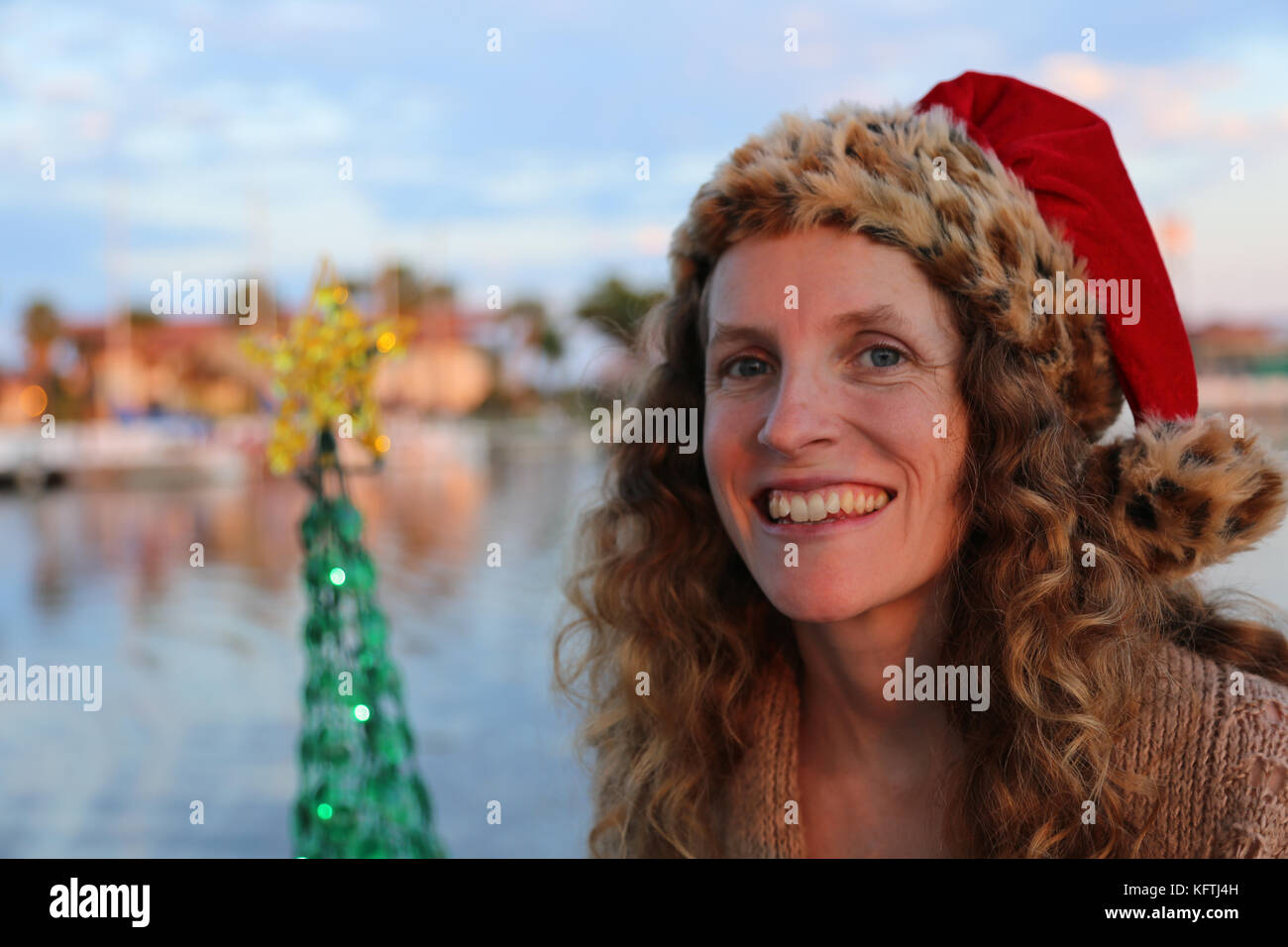 Young lady in a festive holiday Santa hat next to a decorated Christmas tree. - Stock Image
