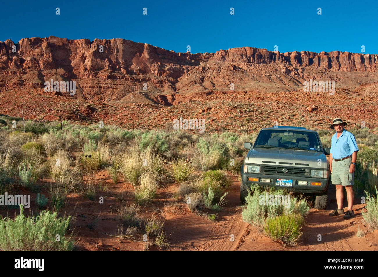 Middle age man, car on dirt track in Jacobs Pool water well area, Paria Plateau escarpment in dist, at Vermilion - Stock Image