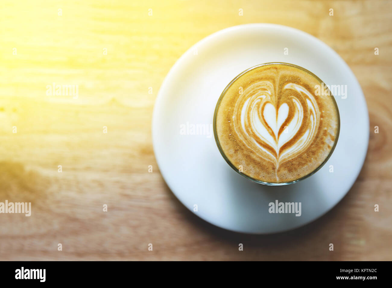 heart drawing on latte art coffee on wood table background - Stock Image