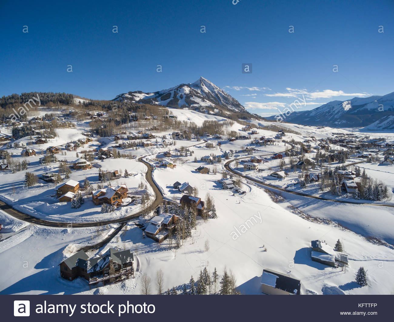 Fresh snow covers the homes and yards of Mount Crested Butte, Colorado with the ski area of Crested Butte Mountain - Stock Image
