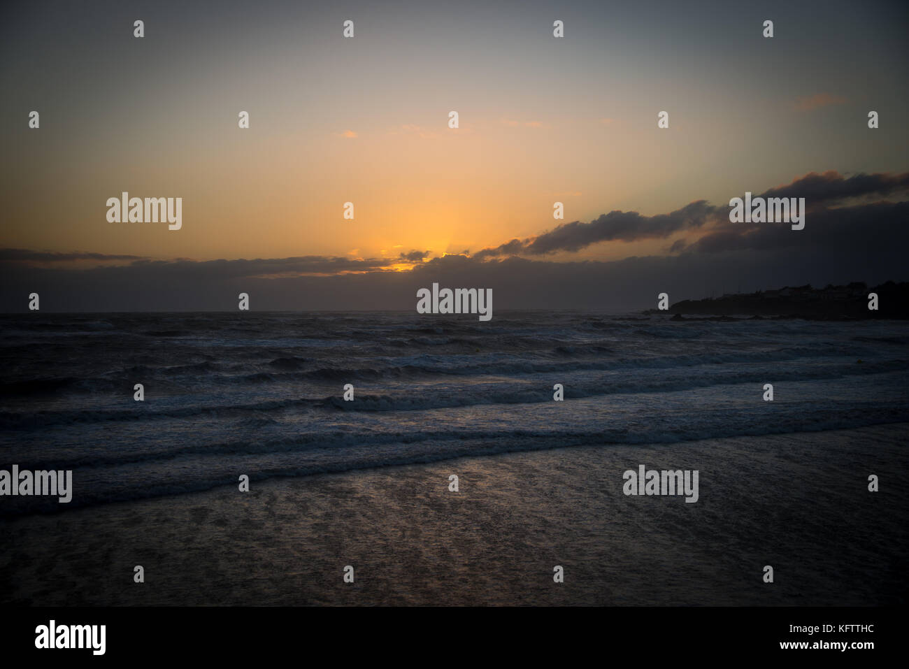 gentle waves on the beach at sunset - Stock Image
