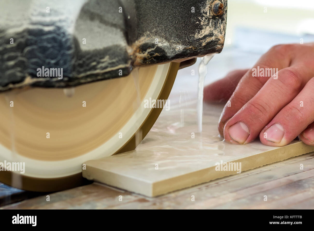Worker hand cutting ceramic tile with water cutting machine close-up ...