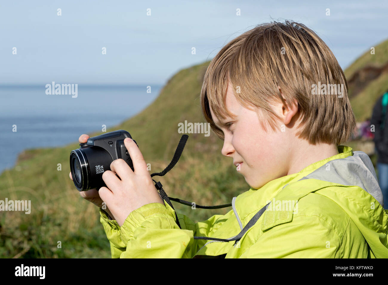 boy taking photos, Giants Causeway, Bushmills, Co. Antrim, Northern Ireland - Stock Image