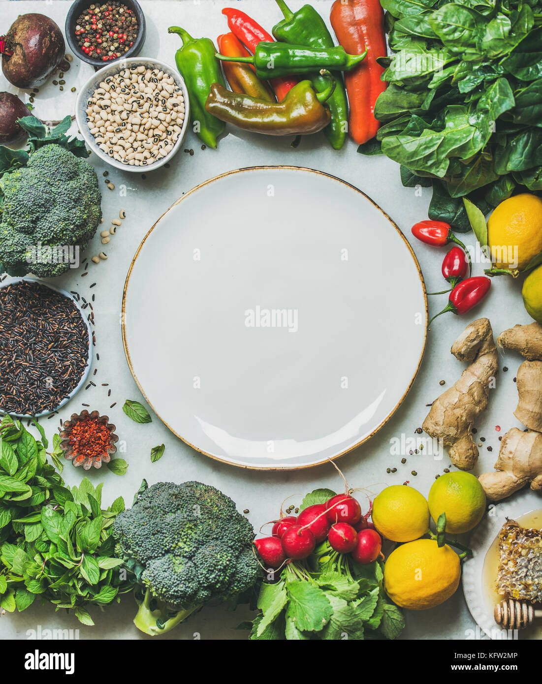 Clean eating healthy cooking ingredients and round plate in center - Stock Image