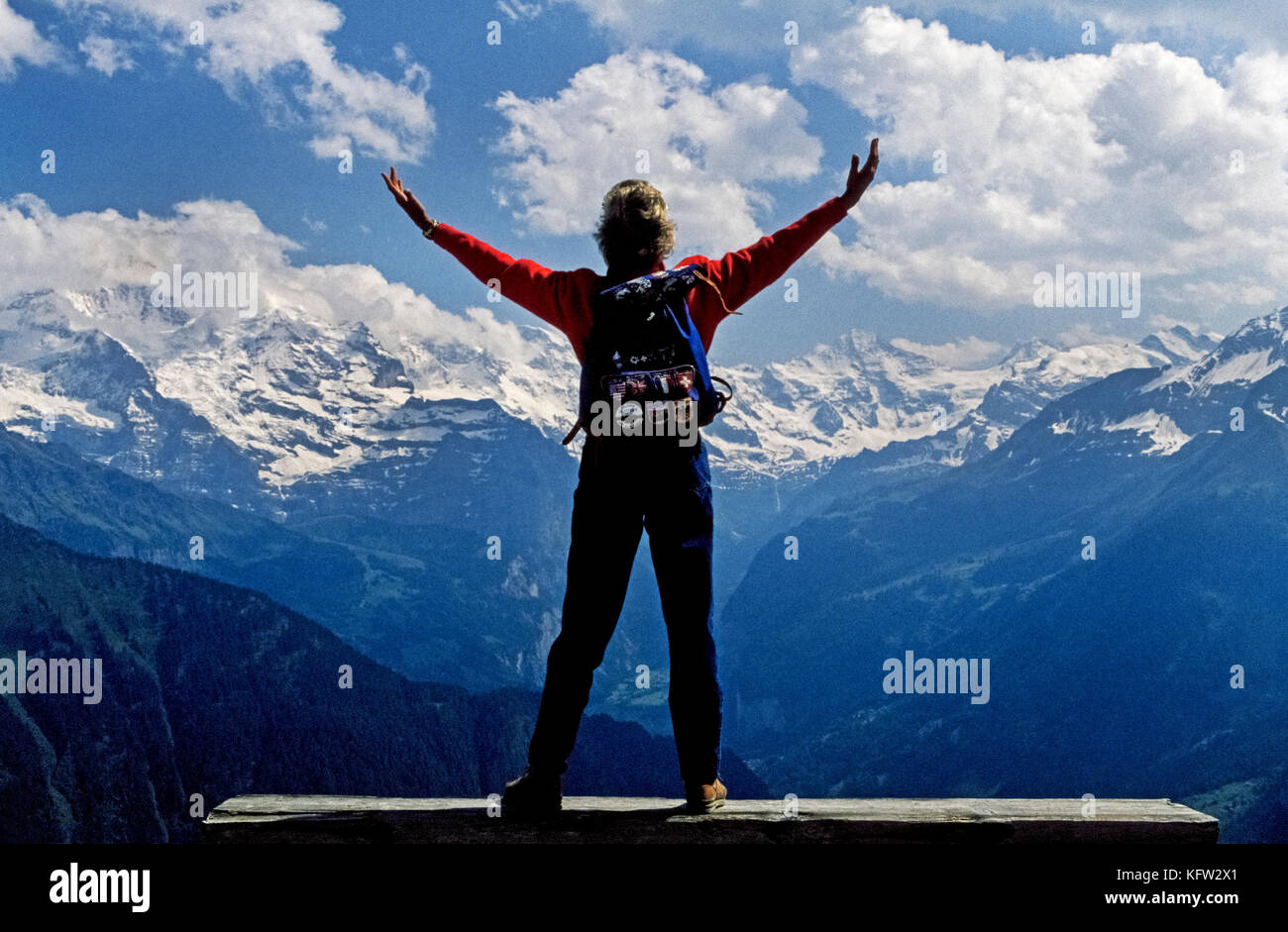 A female visitor on a day-hike raises her arms in exhilaration at the view of the Swiss Alps in the Bernese Oberland, - Stock Image