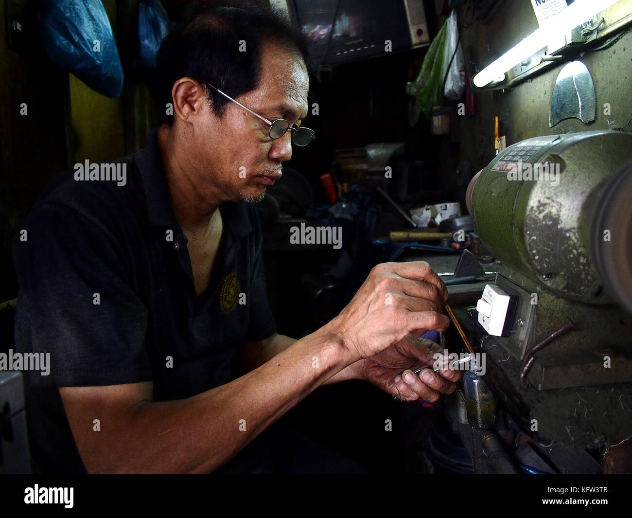 ANTIPOLO CITY, PHILIPPINES - OCTOBER 27, 2017: A worker sharpens a nipper in his repair shop. - Stock Image