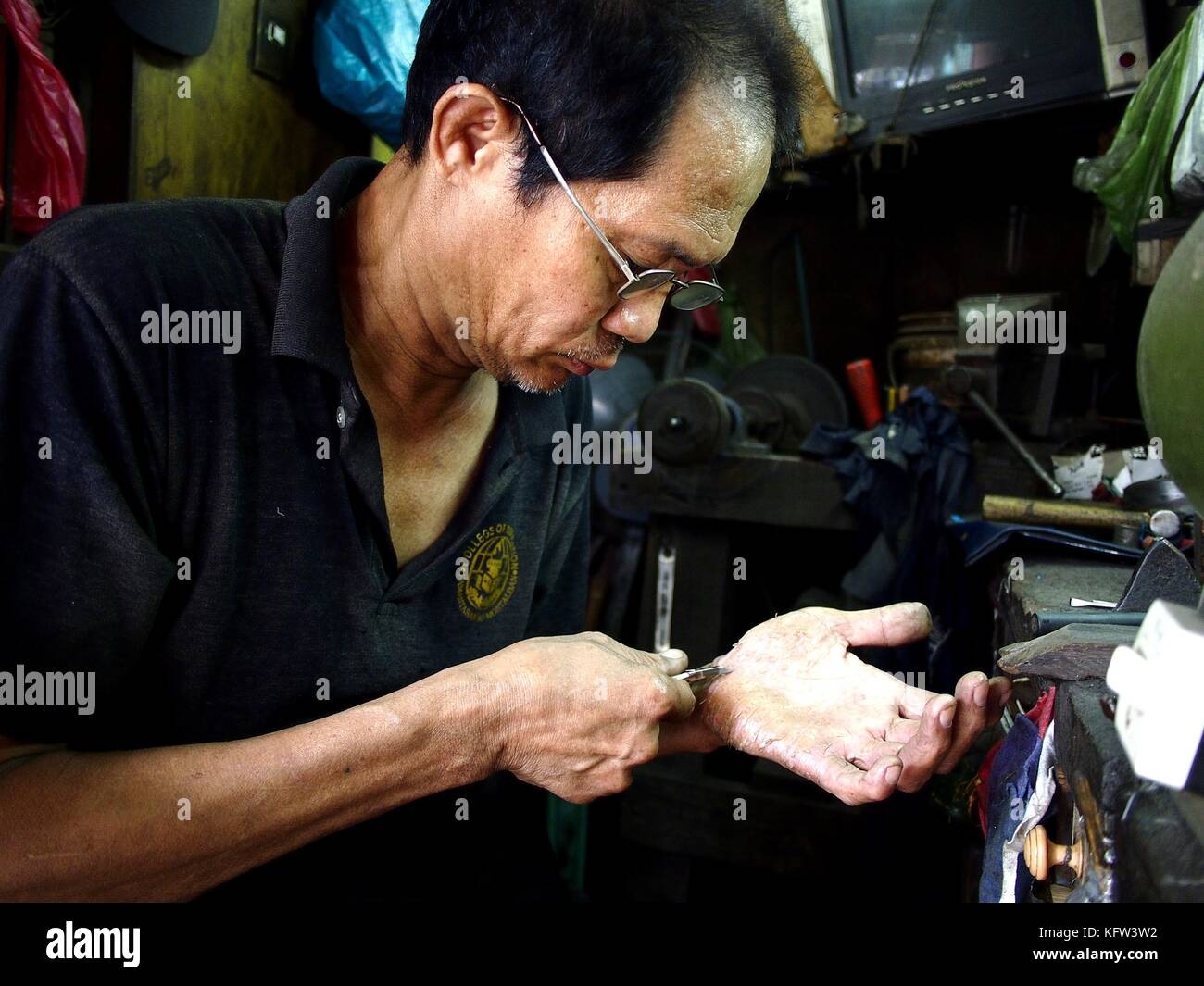 ANTIPOLO CITY, PHILIPPINES - OCTOBER 27, 2017: A worker tests a nipper he sharpened on the palm of his own hands. - Stock Image