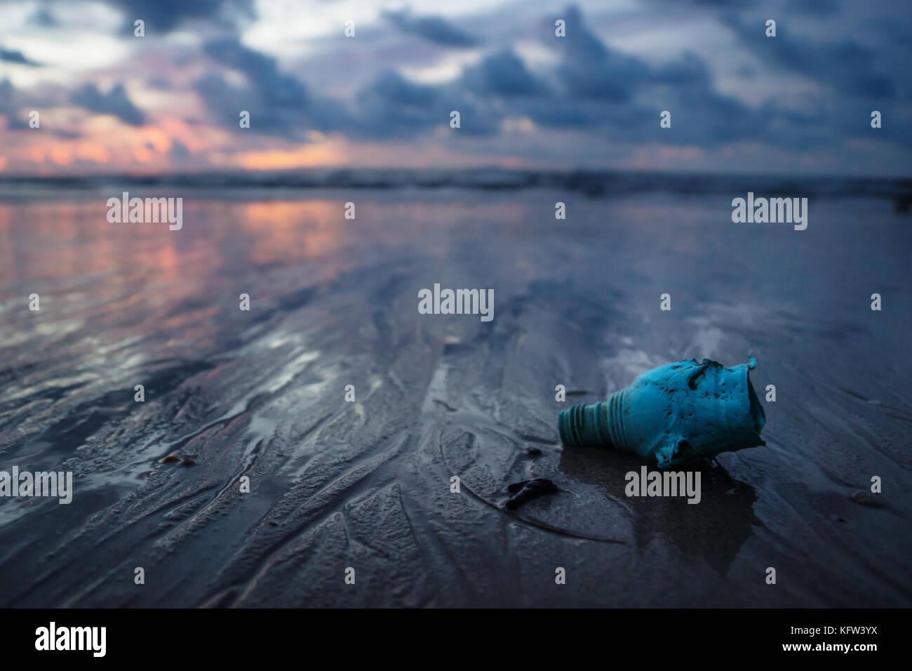Plastic trash littering the ocean at the beach during sunset, Koh Lanta, Thailand - Stock Image