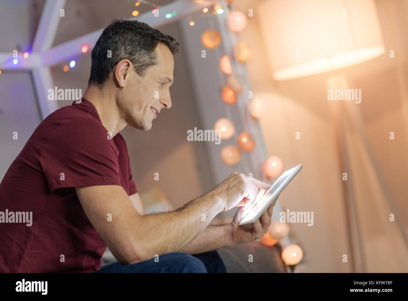 Attentive man playing with tablet - Stock Image
