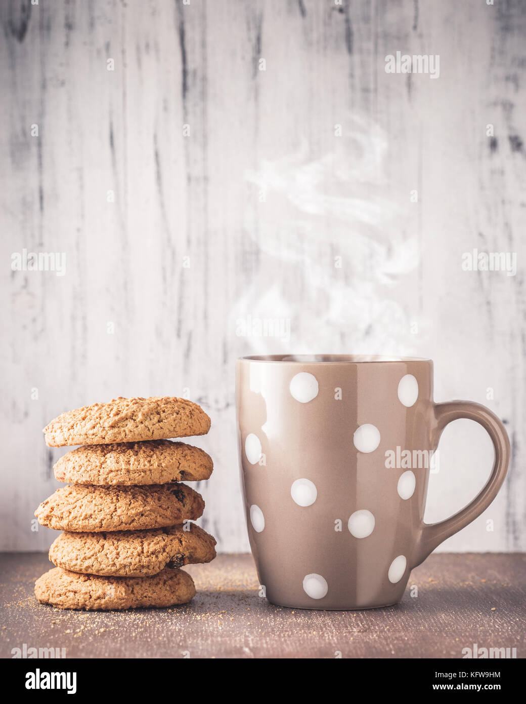 Stack of oat cookies and polka dot mug with hot drink over wooden background - Stock Image