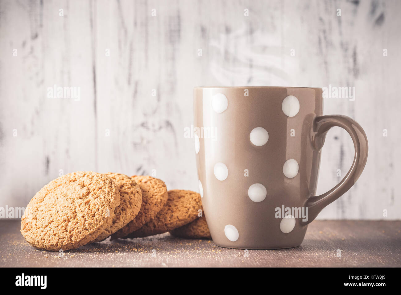 Oat cookies and polka dot mug with hot drink over wooden background - Stock Image