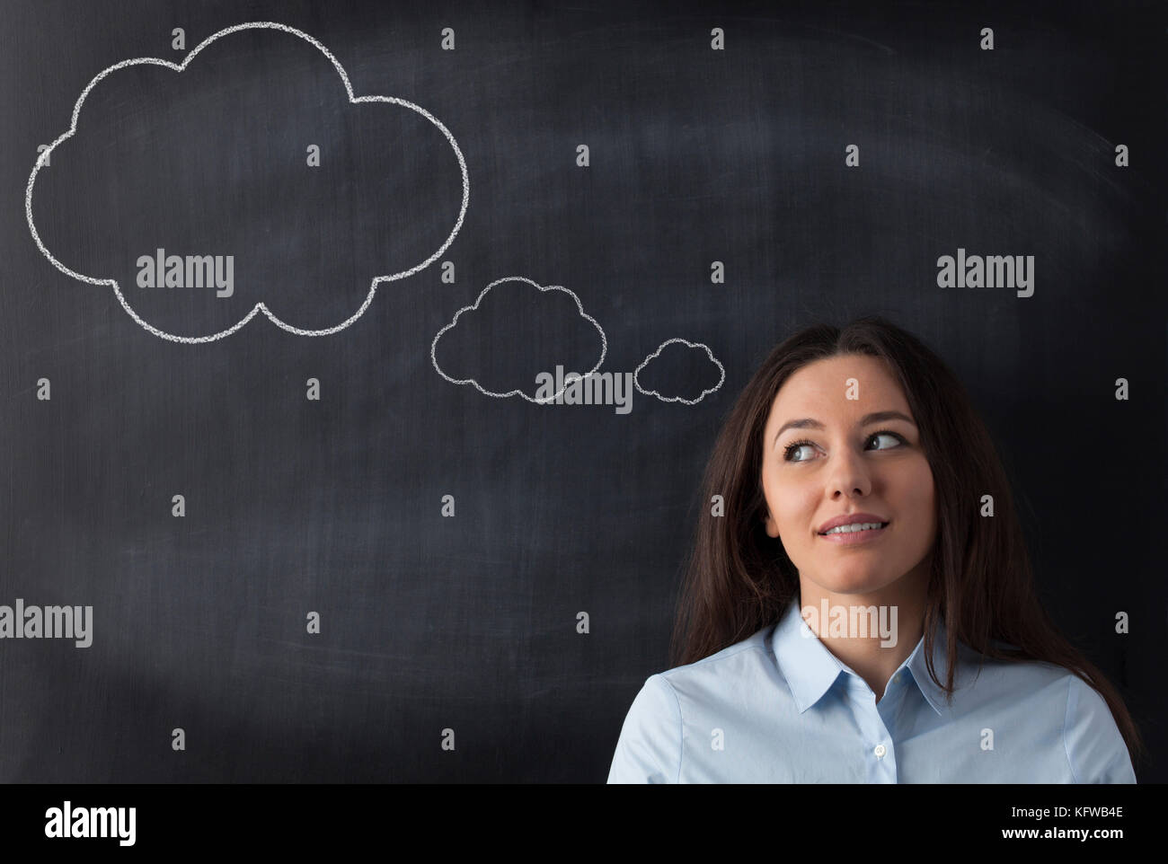 Young businesswoman thinking while standing against cloud chalk drawing on blackboard - Stock Image