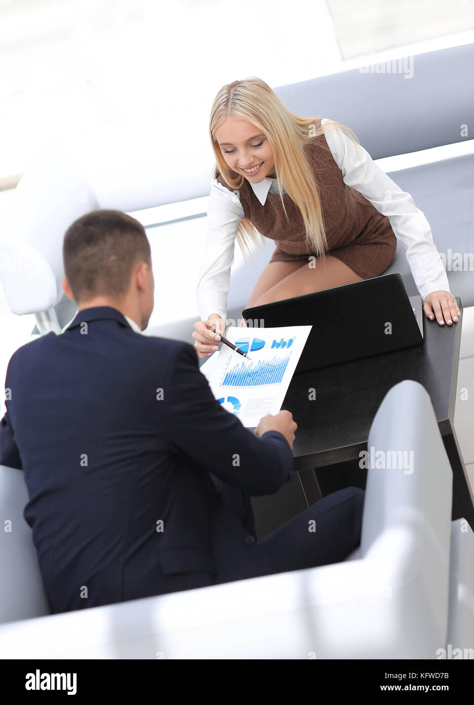 Finance staff discussing financial charts in the lobby of the office. - Stock Image
