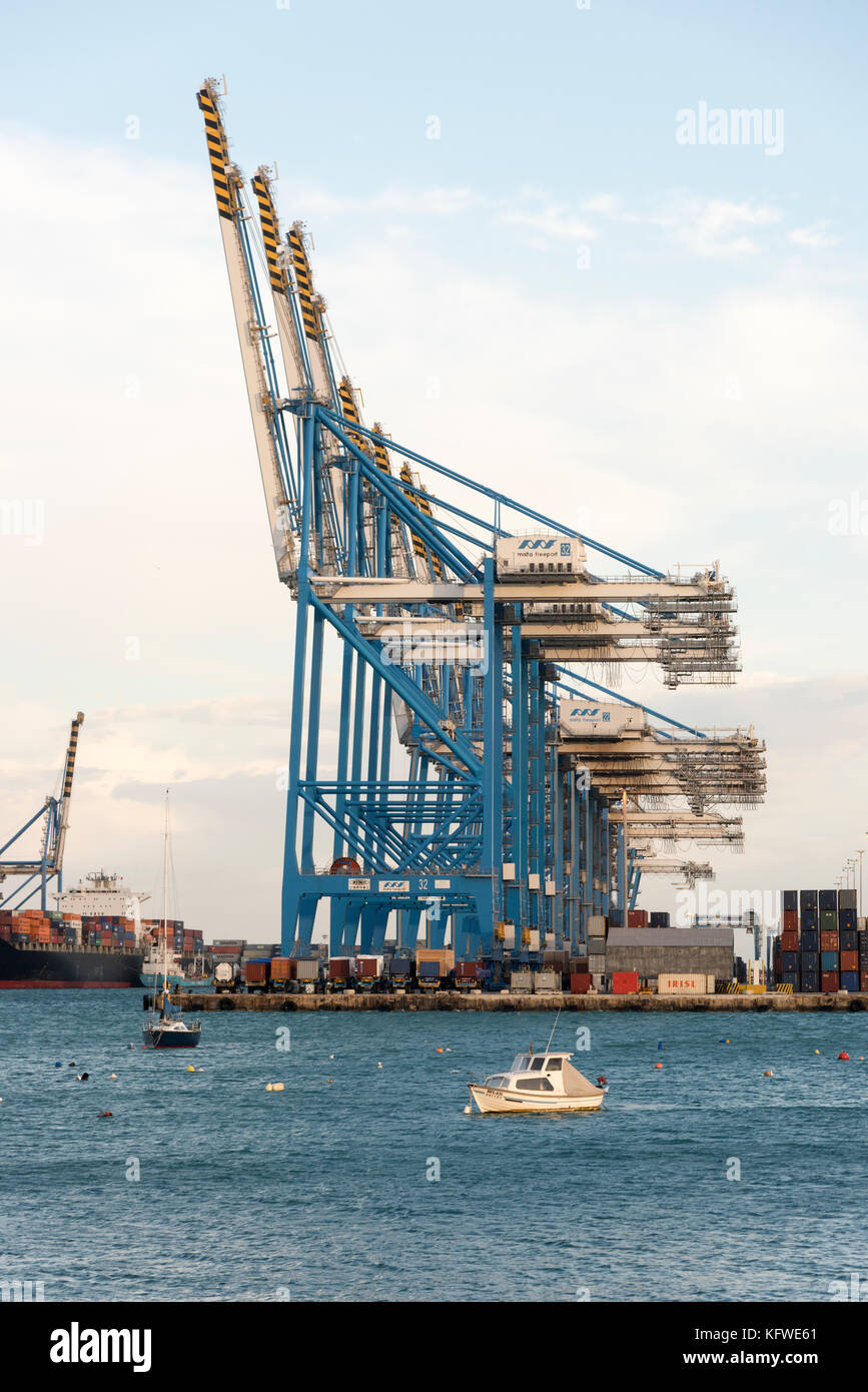 Malta Freeport showing the cranes at the container terminal and shipping port next to the seaside resort of Pretty - Stock Image