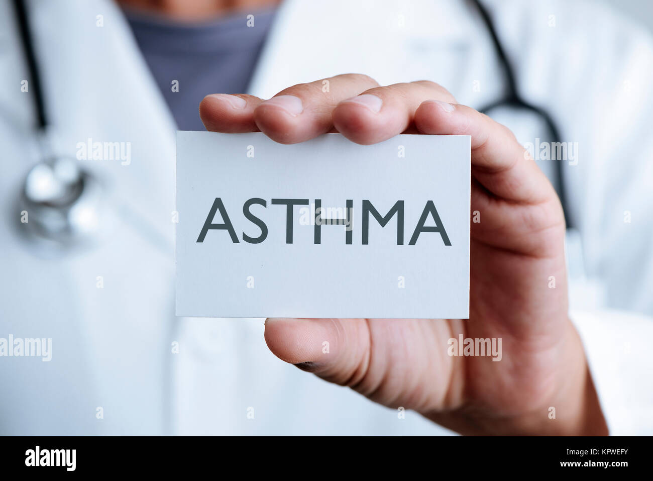 closeup of a young caucasian doctor man in a white coat showing a signboard with the text asthma written in it - Stock Image
