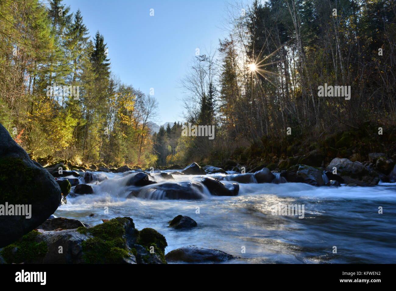 Rivière nommée la Vièze se déversant dans une vallée ensoleillée des Alpes Suisses - Stock Image