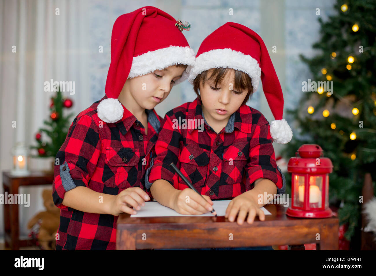 Two adorable children, boy brothers, writing letter to Santa Claus at home - Stock Image