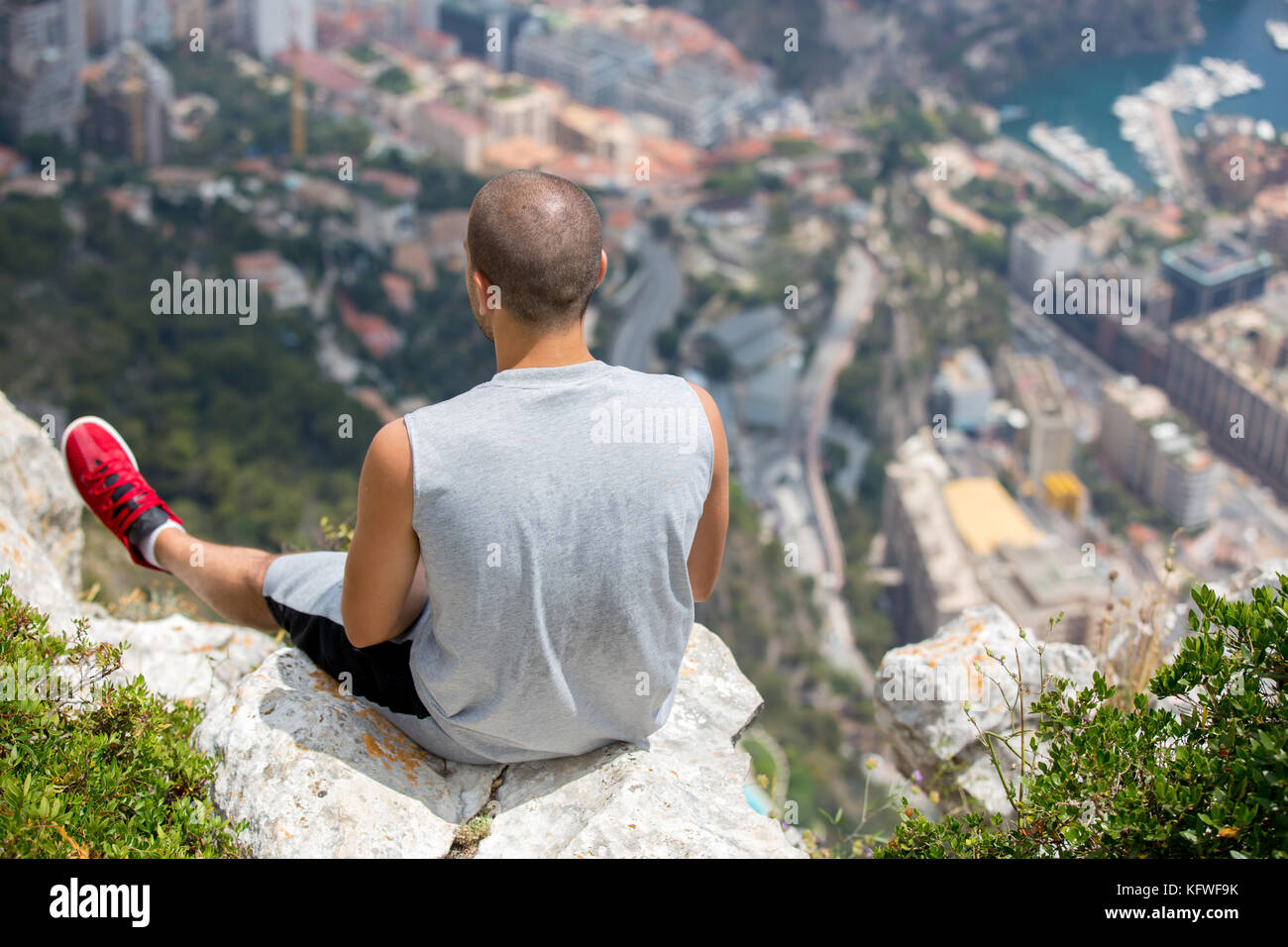 Young man on a hill above Monaco, contemplating the view on a sunny summer day - Stock Image