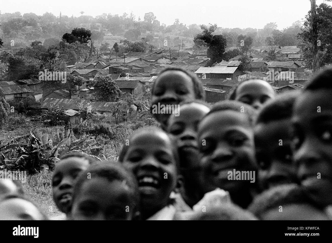 Smiling school boys with shanty town in background, Kampala, Uganda, East Africa. - Stock Image