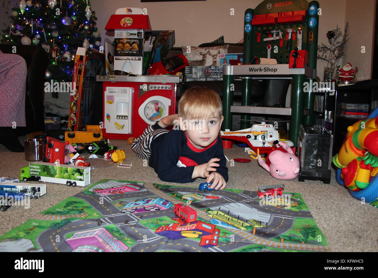 A child opening Christmas presents on Christmas morning - Stock Image