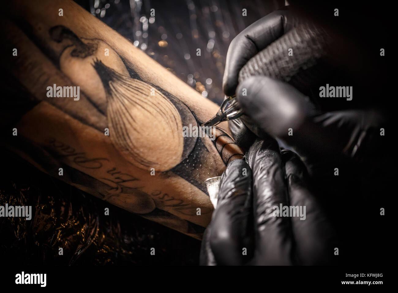 Tattoo master works in black sterile gloves - Stock Image