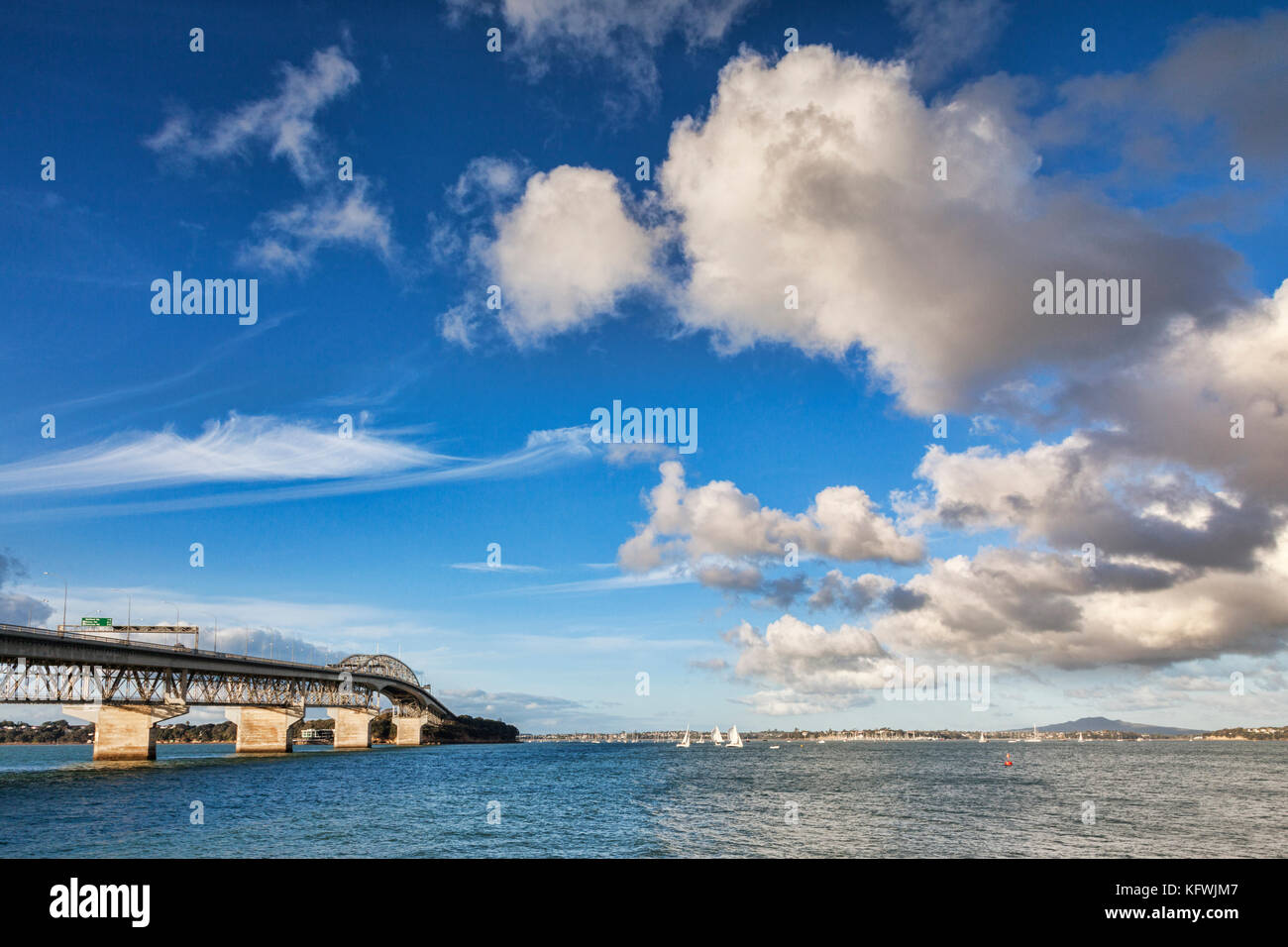 Auckland Harbour Bridge and the Hauraki Gulf, on a great sailing day. In the background is the volcano, Rangitoto - Stock Image