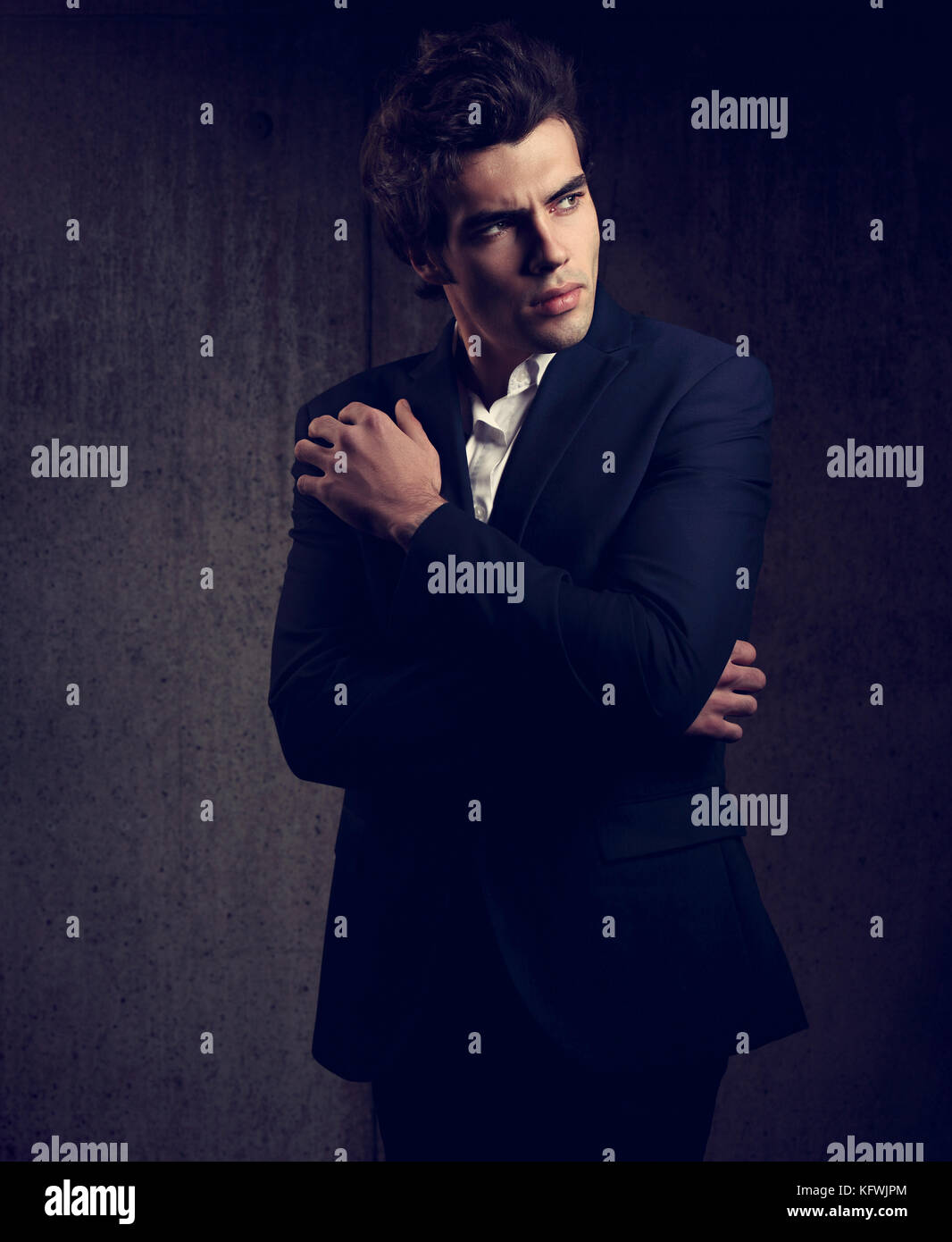 e61c19d4 Charismatic handsome male model posing in blue fashion suit and white style  shirt looking on dark shadow background. Toned closeup portrait