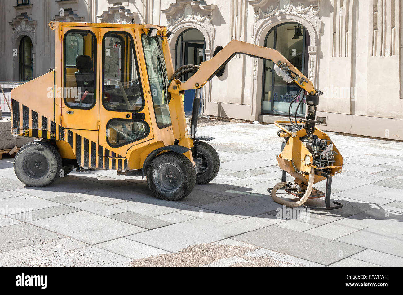 Paving slabs laying machinery. The restoration of paving in the city. - Stock Image